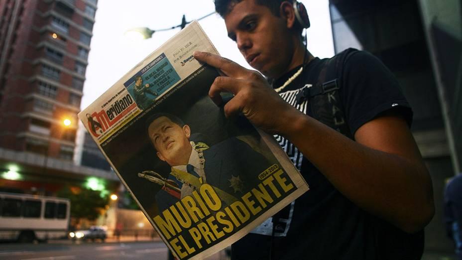 Jovem lê jornal local no dia seguinte à morte do presidente da Venezuela Hugo Chávez, em Caracas