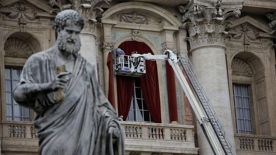 Trabalhadores colocam uma cortina vermelha na bancada central da Basílica de São Pedro, no Vaticano, em preparação à eleição do novo papa ao fim do conclave, que se inicia na terça-feira (12)