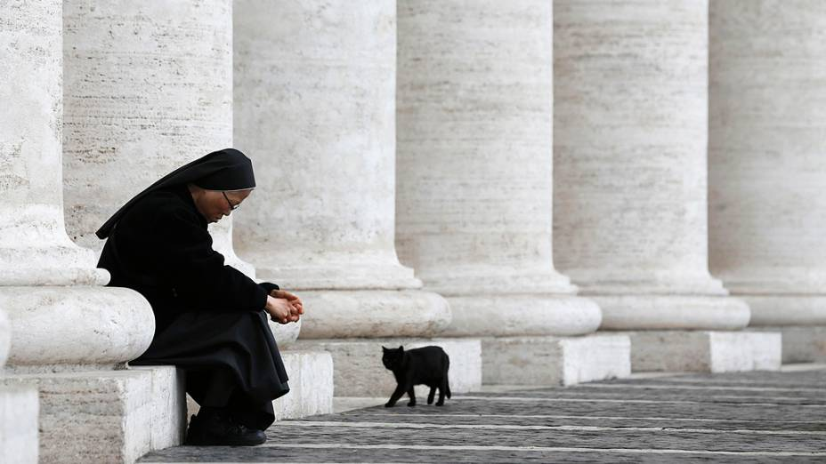 Gato preto caminha ao lado de freira na Praça de São Pedro, no Vaticano