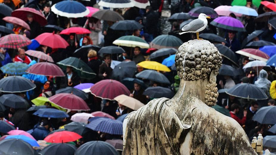 Sob chuva, os fiéis esperam na Praça de São Pedro o possível anúncio do novo Papa