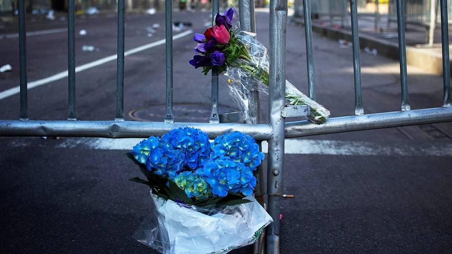 Flores são deixadas nesta terça-feira (16) na grade que bloqueia a Boylston Street, perto da linha de chegada da Maratona de Boston