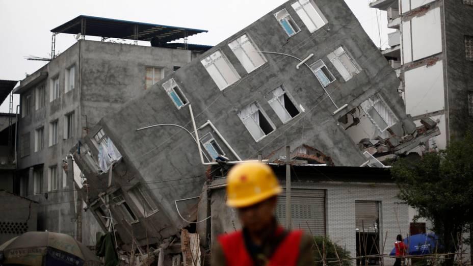 Homem presta socorro na frente de um prédio danificado após o terremoto na cidade Lingguan de município de Baoxing, da província de Sichuan. O terremoto foi o pior dos últimos três anos,  com 208 mortos e  com quase 1.000 feridos graves, na China