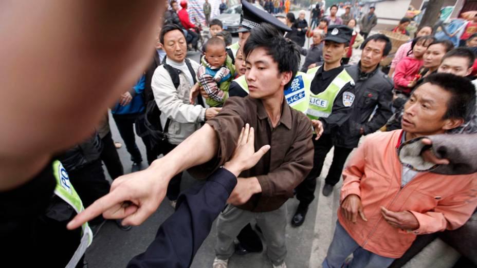 Sobrevivente do terremoto  enfrenta um policial que estava tentando controlar um protesto contra a falta de operações de resgate na aldeia de Chaoyang, depois do terremoto de sábado, em Lushan condado de Yaan, na China