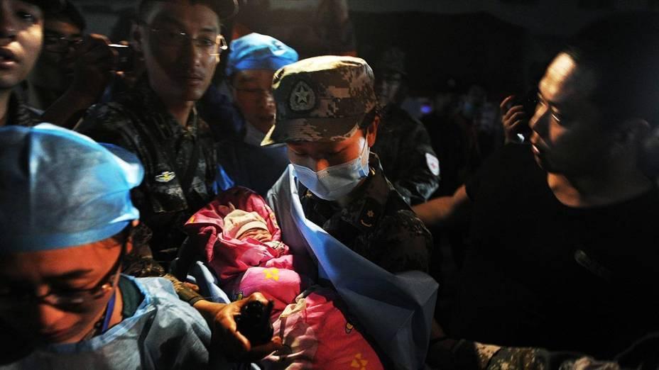 Recém-nascido em uma tenda de socorro é atendido pela equipe médica após o terremoto que atingiu  o condado de Lushan, na província de Sichuan, China