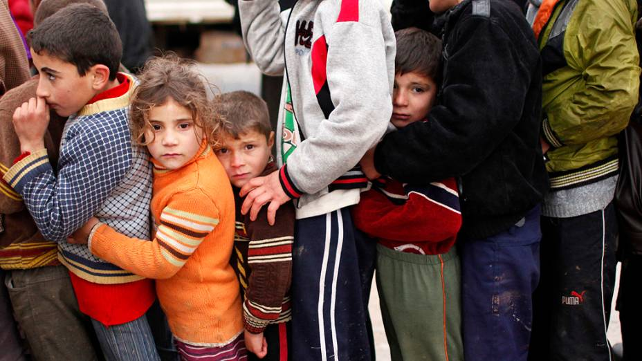 Crianças esperam para receber alimentos e ajuda em campo de refugiados na cidade de Bab al-Salam, na Síria
