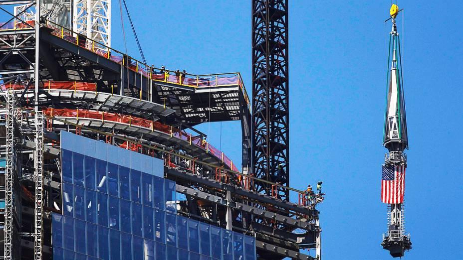 Sessão final da torre que vai coroar o One World Trade Center é levantada com a bandeira dos Estados Unidos. O One World Trade Center é o edifício principal do novo complexo do World Trade Center em Lower Manhattan, em Nova York
