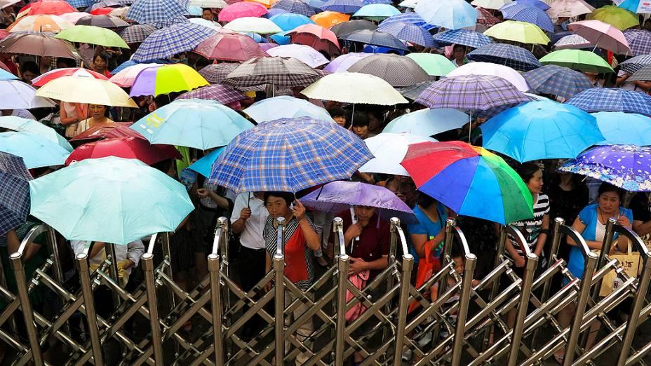 Sob chuva, centenas de pais esperam longas horas pela saída dos filhos das salas de exame