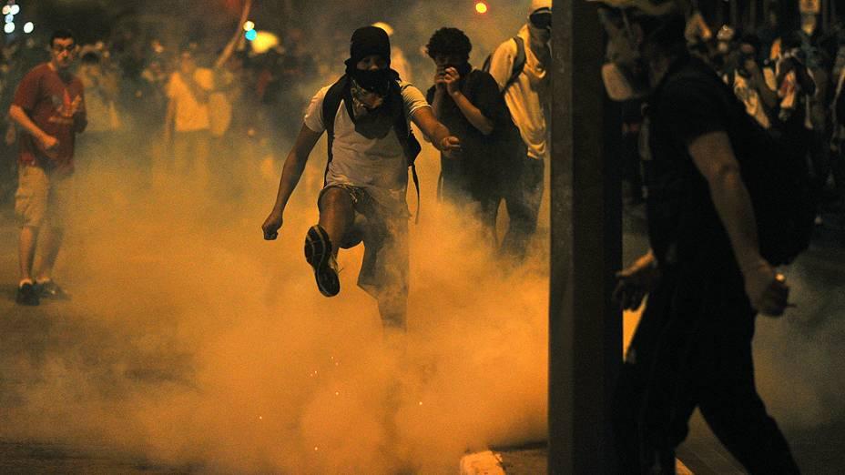 Manifestante chuta uma bomba de gás lacrimogêneo durante confrontos com a polícia do lado de fora do estádio Mineirão, em Belo Horizonte, na quarta-feira (26)