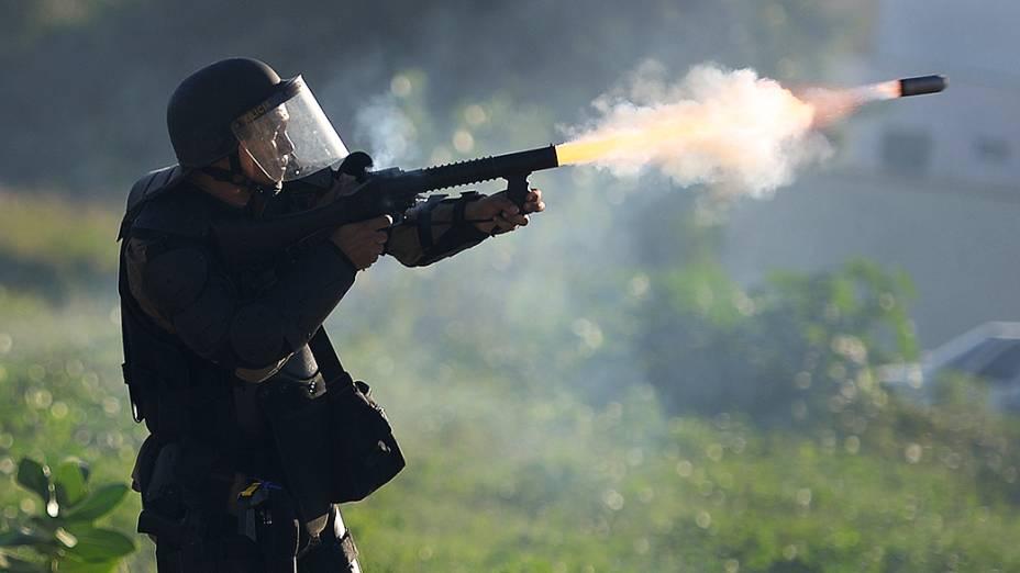 Policial joga uma bomda de gás lacrimogêneo contra manifestantesno perímetro de segurança de dois quilômetros do estádio Castelão, em Fortaleza, onde Espanha e Itália jogam semifinal da Copa das Confederações, em 27 de junho