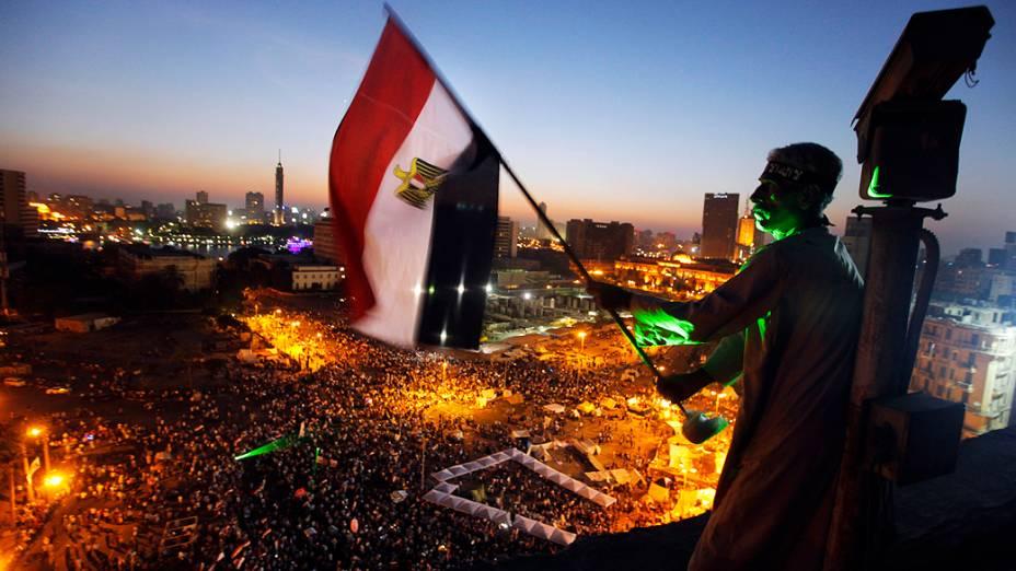 Manifestante segura a bandeira egípcia no alto de prédio perto da Praça Tahrir, local de reunião dos opositores do presidente Mohammed Mursi, na sexta-feira (28)