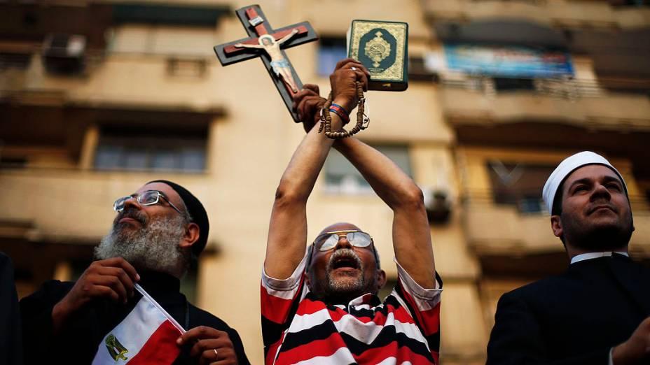 Manifestante segura uma cruz e o livro do Alcorão durante um protesto exigindo a renúncia do Mohamed Mursi, no dia em que o presidente recebeu um ultimato do Exército