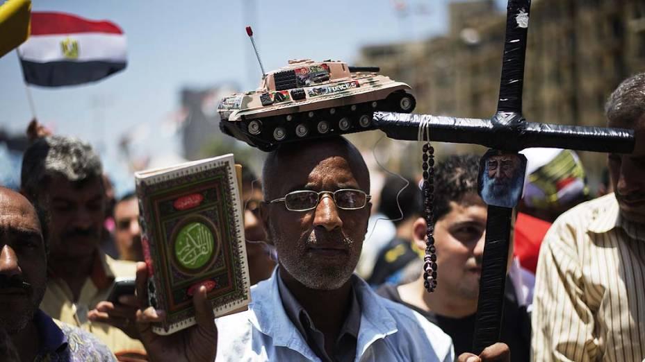 Homem com um tanque de brinquedo na cabeça, segura uma cruz e uma cópia do Corão, caminha até a praça Tahrir, no Cairo nesta quinta-feira (04), depois de uma noite de celebrações após a derrubada do deposto presidente egípcio Mohammed Mursi