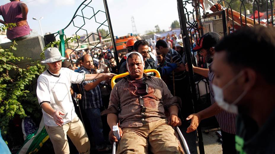 Homem ferido é transferido de cadeiras de rodas a hospital improvisado, após tiroteio próximo da Guarda Republicana do Egito, no Cairo; ao menos 34 morreram