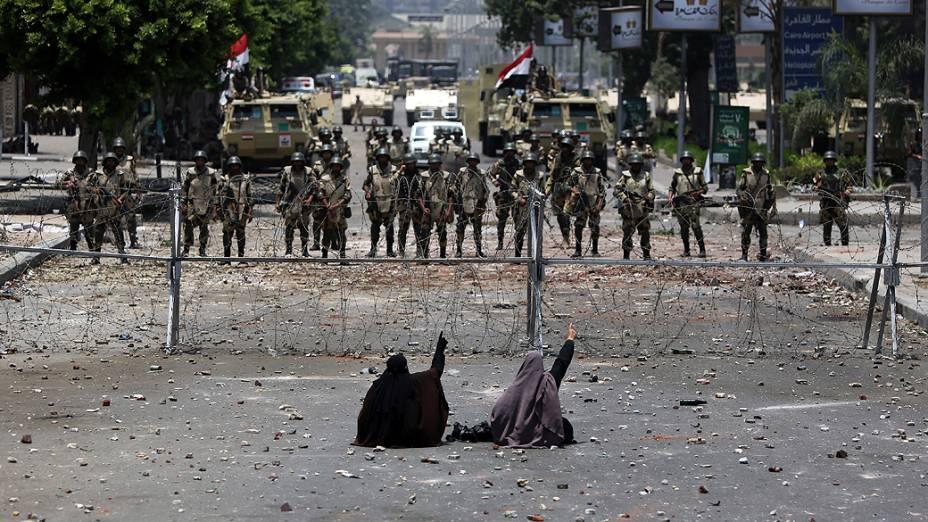 Apoiadores do presidente deposto do Egito, Mohamed Morsi, sentam em frente a barreira de arame farpado que bloqueia o acesso à Guarda Republicana no Cairo