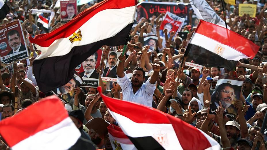 Apoiadores do presidente deposto do Egito, Mohamed Morsi, empunham bandeiras e cartazes a seu favor, próximo à Guarda Republicana no Cairo nesta segunda-feira (8)