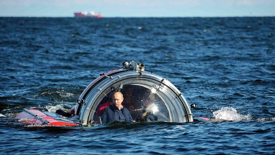 """O presidente da Rússia, Vladimir Putin é visto através do vidro de C-Explorer 5 submersível após um mergulho para ver os restos da fragata naval """"Oleg"""", que afundou no século 19, no Golfo da Finlândia, no Mar Bálticonesta segunda-feira (15)"""