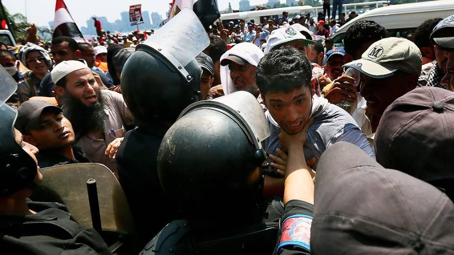 Apoiador do presidente deposto do Egito, Mohamed Mursi entra em confronto com a polícia de choque nesta quarta-feira (17), durante um protesto na estrada que conduz ao marco praça Tahrir, no Cairo