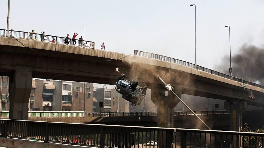 Um veículo da polícia é empurrado para fora da ponte 6 de outubro por manifestantes partidários do presidente deposto Mohammed Mursi, no Cairo, nesta quarta-feira (14)