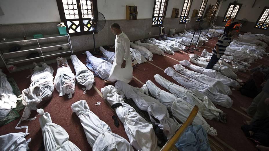 Homem caminha entre corpos nesta quinta-feira(15), em uma mesquita no Cairo, depois de uma repressão sobre os acampamentos de protesto dos partidários do deposto presidente islâmico Mohamed Mursi, no Egito