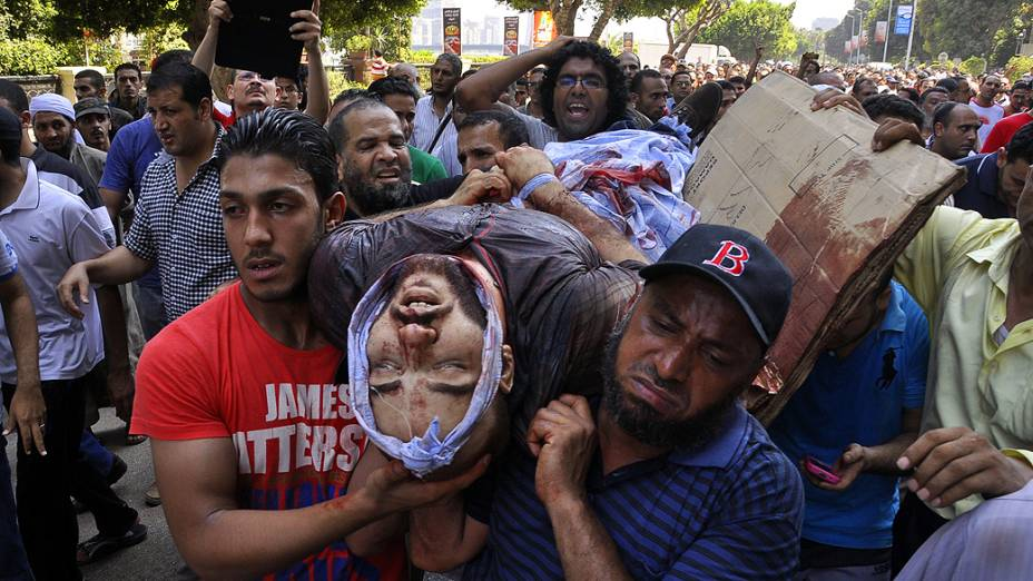 Manifestantes carregam homem ferido durante os protestos no Cairo, nesta sexta-feira (16)