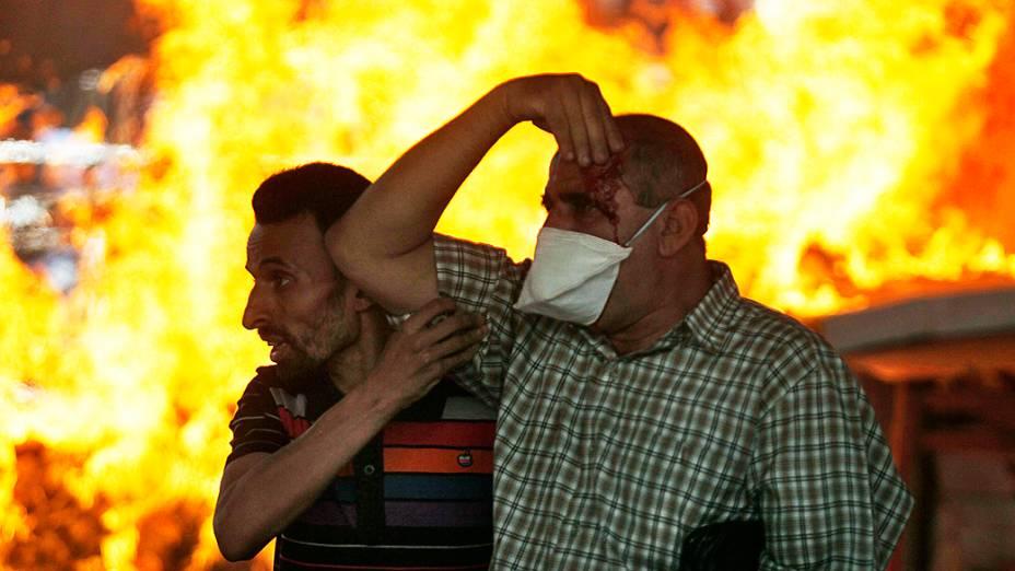 Manifestantes ajudam pessoas feridas durante os confrontos no Cairo, nesta sexta-feira (16)