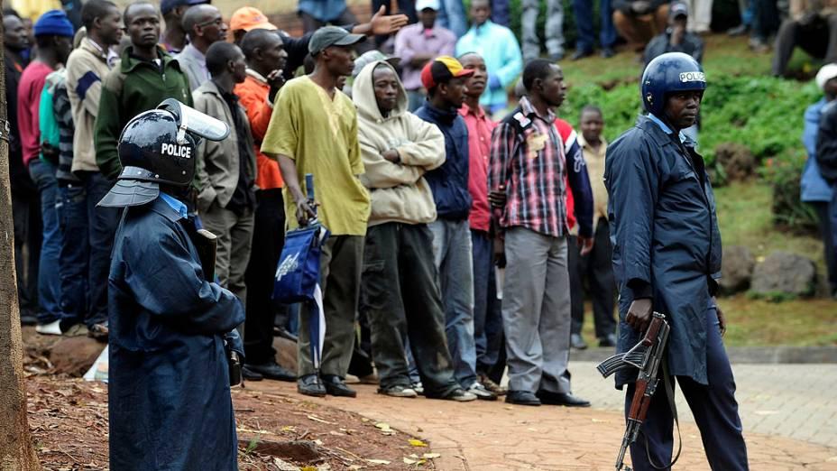 Policiais afastam as pessoas do lado de fora do shopping Westgate em Nairobi. A policia entrou em um tiroteio com os militantes da milícia islâmica Al-Shabab dentro de um shopping de luxo Nairobi em 22 de setembro em um último esforço para acabar com o cerco que deixou pelo menos 69 mortos e 200 feridos, no Quênia