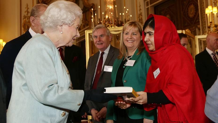 A jovem ativista paquistanesa Malala Yousafzai entrega uma cópia de seu livro para a rainha Elizabeth II, no Palácio de Buckingham, em Londres