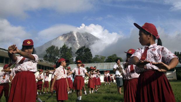 <p>Em Karo, na Indonésia, estudantes fazem exercícios com erupção do Monte Sinabung ao fundo</p>