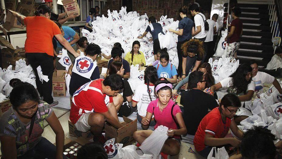 Voluntários embalam alimentos para vítimas do tufão Haiyan em Manila, nas Filipinas