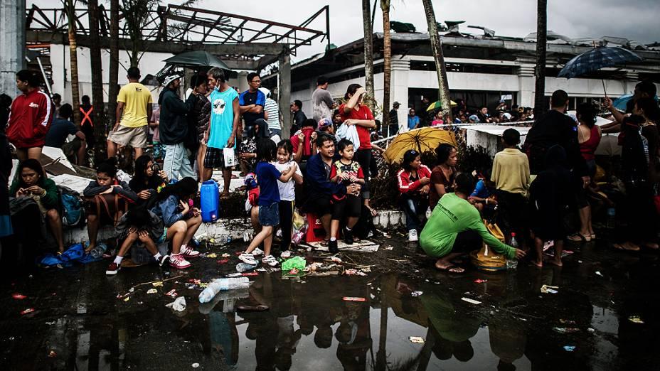 Moradores esperam por comida no aeroporto de Tacloban, nas Filipinas
