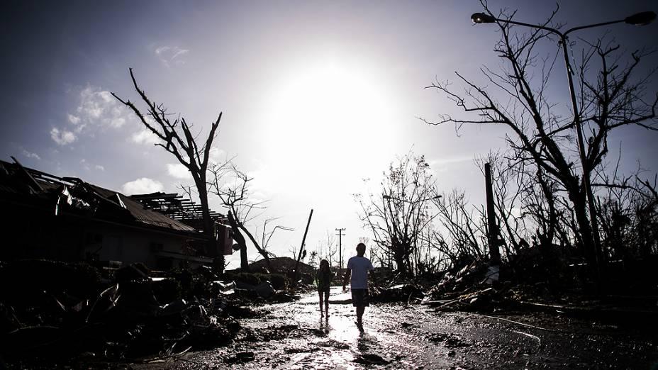Sobreviventes percorrem as ruínas de um bairro afetado pelo tufão nos arredores de Tacloban, nas Filipinas