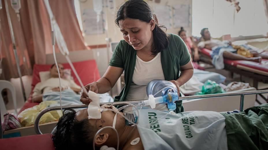 Mulher cuida de seu marido em hospital de Tacloban, nas Filipinas, nesta sexta-feira (15)