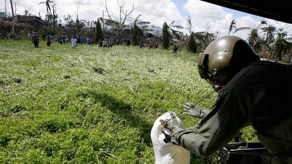 Sobreviventes tentam pegar comida distribuída pelos soldados filipinos nos arredores da cidade de Tacloban
