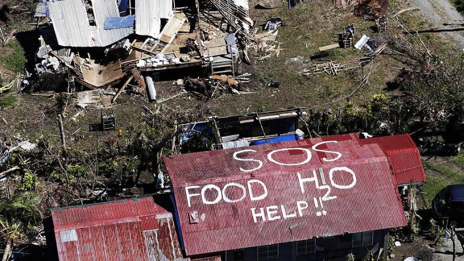 Imagem aérea mostra um pedido de socorro escrito no telhado de uma casa na cidade de Tacloban, nas Filipinas, nesta sexta-feira (15)