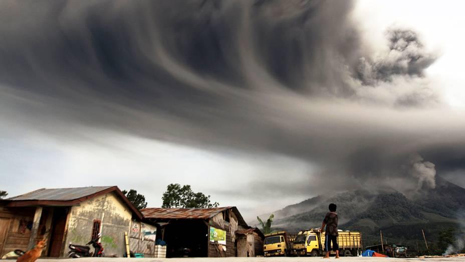 <p>Mulher observa fumaça expelida pelo vulcão Sinabung que alcançou 8 km de altura, no distrito de Karo, na Indonésia</p>