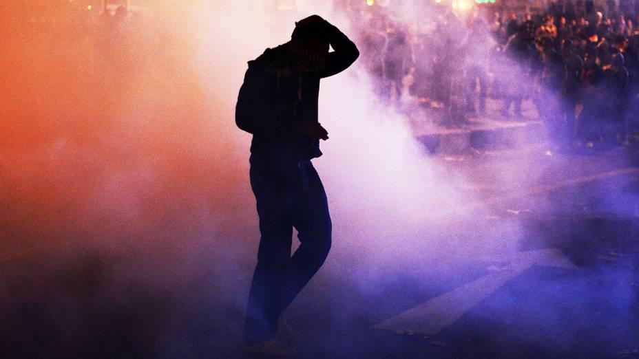 Manifestante recebe gás lacrimogêneo durante confronto que marca o aniversário dos protestos contra os militares em 2011, na praça Tahrir, no Cairo, Egito