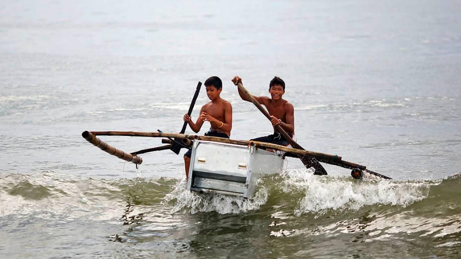 Garotos conduzem barco feito de uma geladeira quebrada e bambu na praia em Tanauan, nas Filipinas, nesta quarta-feira (20)