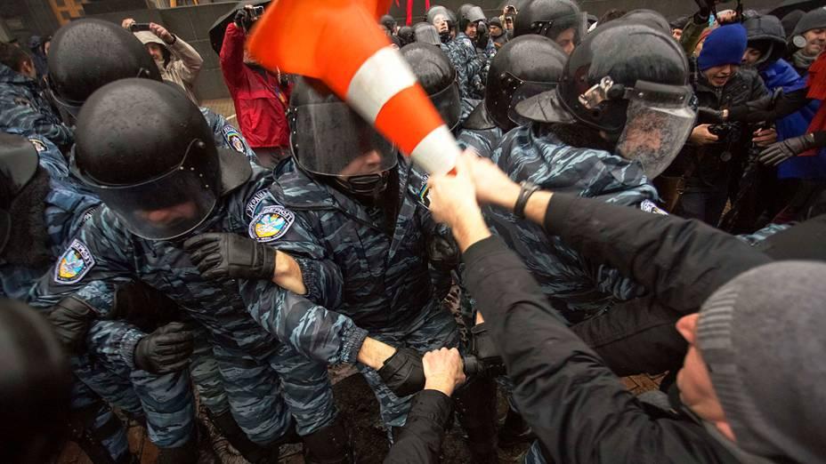 Manifestante entra em confronto com a polícia de choque durante um comício de apoio a integração na União Européia, na frente do gabinete dos ministros em Kiev, na Ucrânia