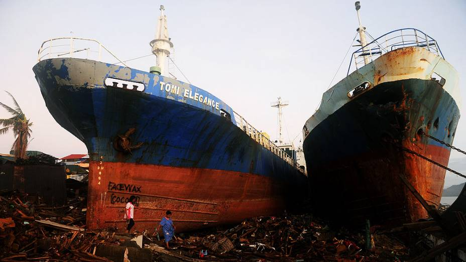 Sobreviventes do tufão Haiyan andam perto de navios arrastados, nas Filipinas
