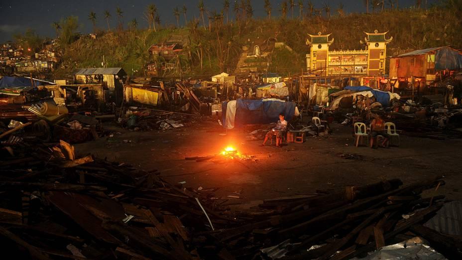 Homem repousa sobre uma cadeira entre casas destruídas pela passagem do supertufão Haiyan em Tacloban, província de Leyte, nas Filipinas