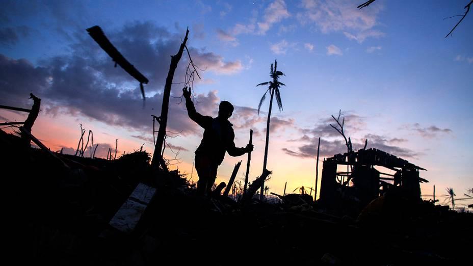 Homem entre os destroços de um bairro arruinado pela passagem do supertufão Haiyan na cidade Palo Leyte, nas Filipinas
