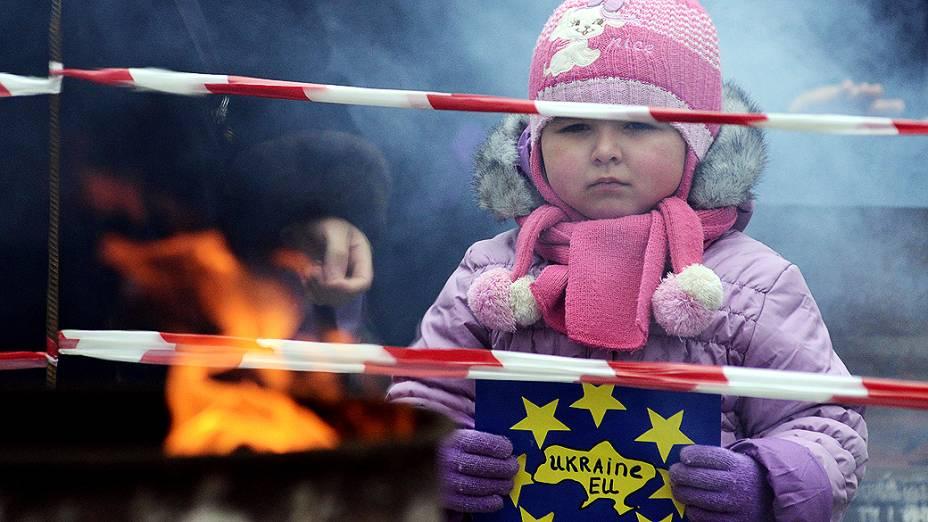 """Criança segura cartaz dizendo """"Ucrânia-UE"""" durante uma manifestação do movimento pró-europeu na cidade de Ivano-Frankivsk, em resposta à decisão do governo ucraniano de desfazer um pacto chave com o União Europeia após sofrer pressão da Rússia"""