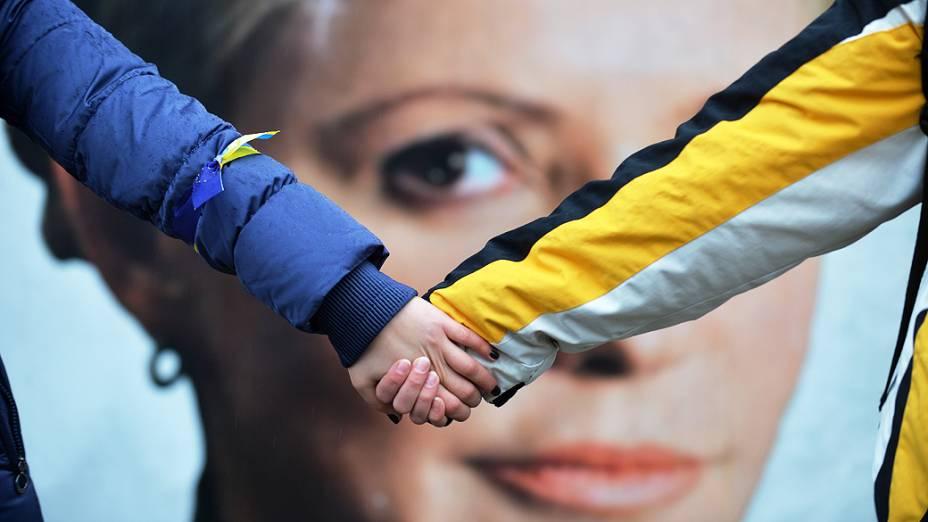 Estudantes dão as mãos simbolizando a união da Ucrânia com a União Europeia em frente de tendas montadas pelos partidários de Yulia Tymoshenko, em Kiev, na Ucrânia