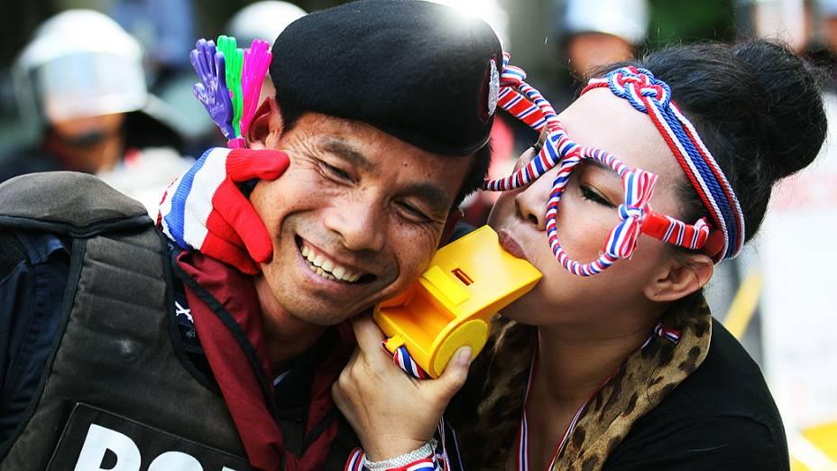 Manifestante protesta contra o governo do lado de fora da sede do partido da primeira-ministra da Tailândia, em Bangcoc