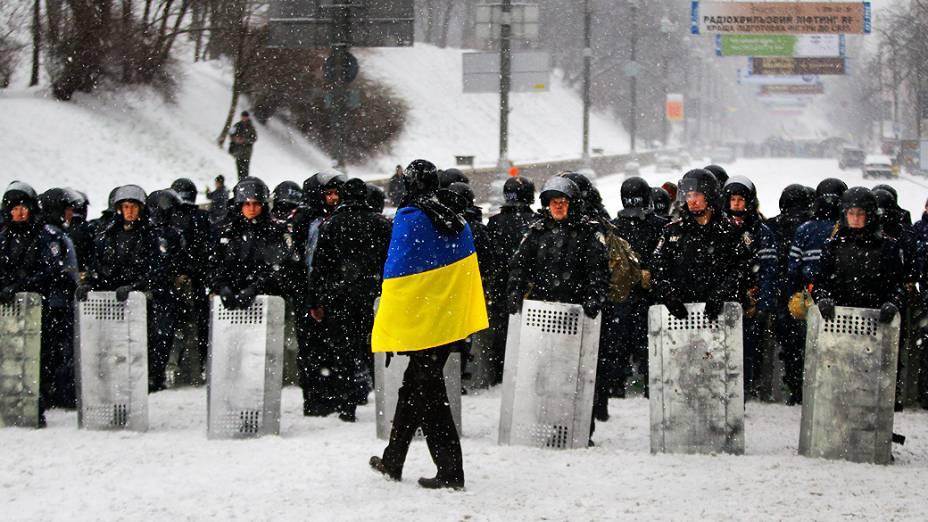 Manifestante observa policiais na praça da Independência, em Kiev (Ucrânia)
