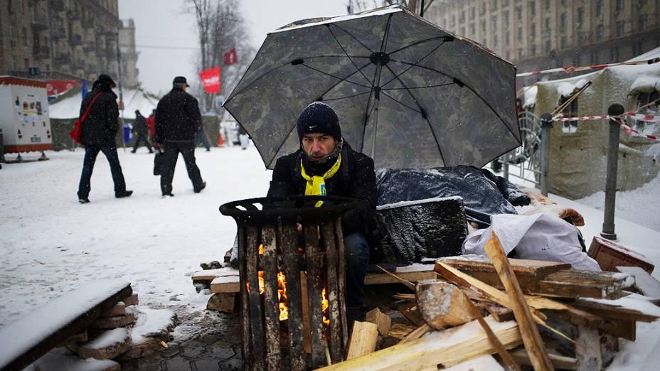Manifestante se aquece na manhã desta segunda-feira (9) enquanto guarda barricada de protesto, na praça da Independência, em Kiev (Ucrânia)