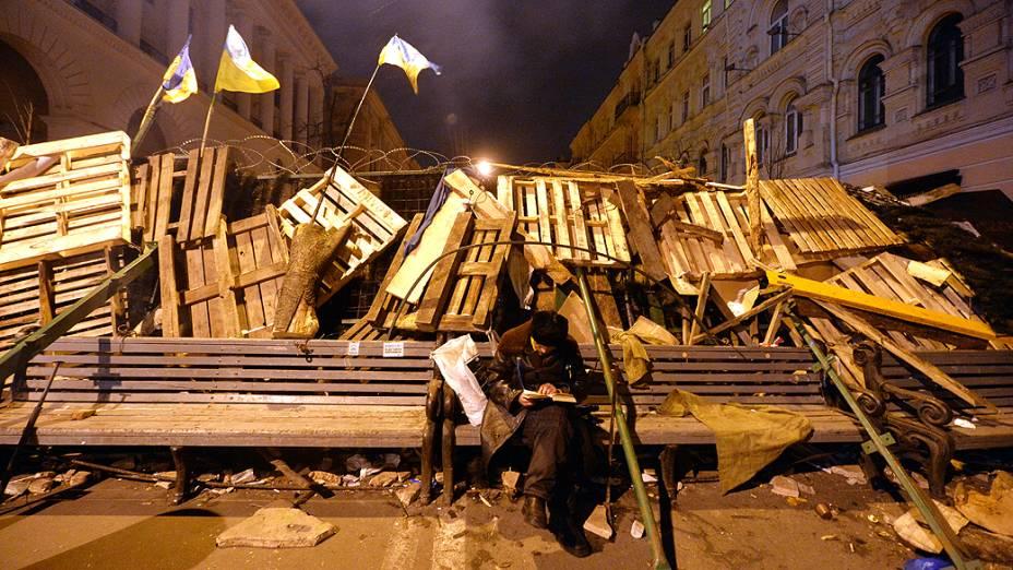Um manifestante lê na madrugada desta segunda-feira (9) enquanto guarda barricada de protesto, na praça da Independência, em Kiev (Ucrânia)