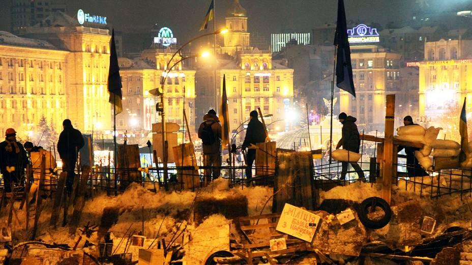 Manifestantes protegem barricada na Praça da Independência de Kiev, após ação da polícia para retirá-los do local