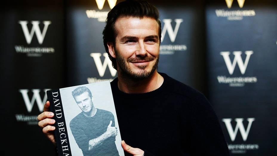 O ex-jogador de futebol David Beckham posa com livro que leva seu nome em uma livraria de Londres, Inglaterra