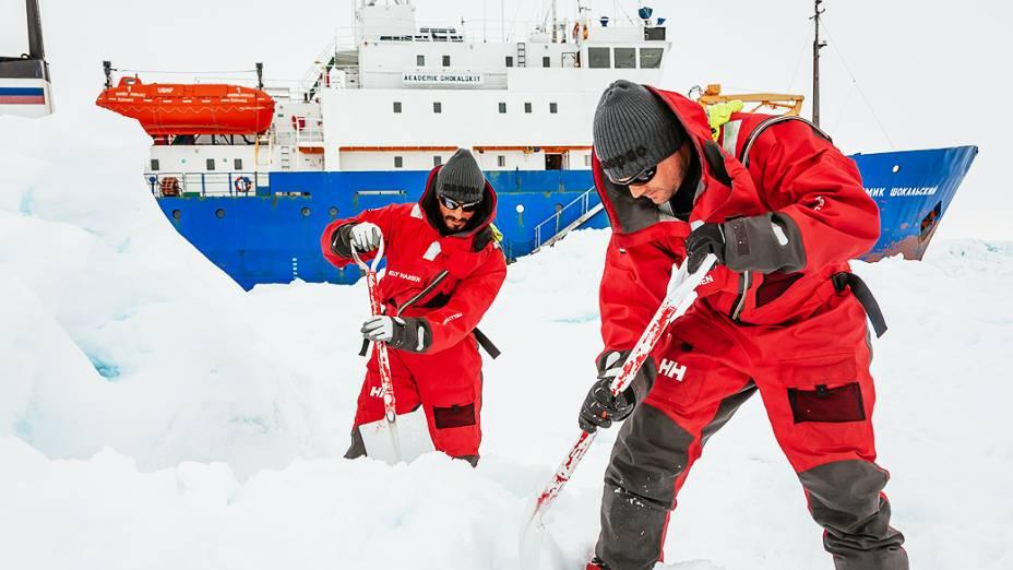 Tripulantes tentam quebrar neve ao redor do navio russo russo MV Akademik Shokalskiy, na Antártida